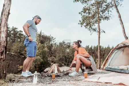 Utile femme bouclée aider son homme allumant le feu près du lac dans la forêt