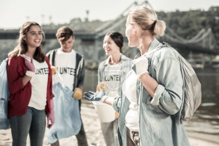 Photo for Garbage bags. Company of teacher and students walking with garbage bags cleaning up the trash while volunteering together - Royalty Free Image