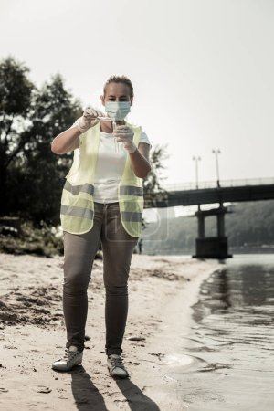 Worker of sanitary hygienic service wearing mask holding test tubes with river water