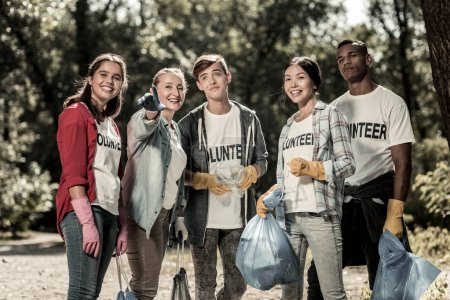 Photo for Garbage bags. Active young volunteers holding garbage bags with trash after cleaning up the forest on weekend - Royalty Free Image