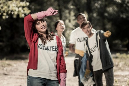 Chica morena usando guantes rosados sintiéndose cansada después de ser voluntaria todo el día