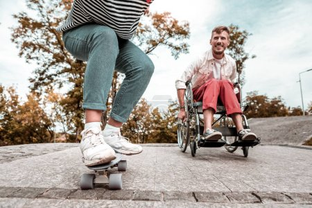 Photo for Competition. Enthusiastic active disabled man riding his modern wheelchair and competing with young person on the penny board - Royalty Free Image