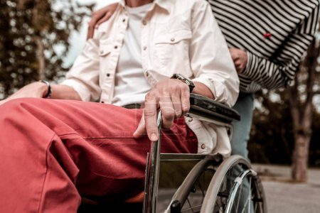 Photo for Man in wheelchair. Young man sitting in the wheelchair and putting his hand on the wheel while being outdoors - Royalty Free Image