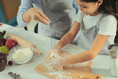 Cute little girl making a dough with mother