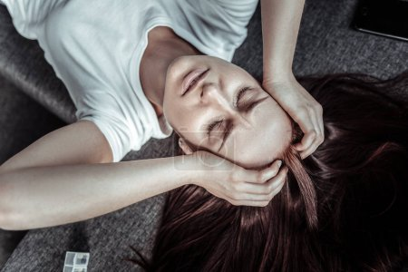 Photo for Having rest. Sad young woman keeping eyes closed and raising hands while touching head - Royalty Free Image
