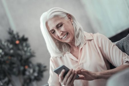 Pleasant delighted woman using mobile gadget