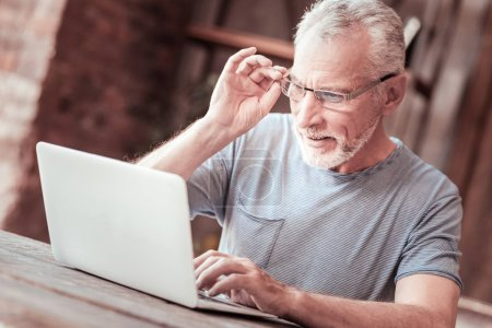 Photo for Full of interest. Close up of attentive elderly man touching his glasses rim while looking at the laptop screen and expressing concern - Royalty Free Image