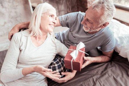 Photo pour Une agréable surprise. Gros plan de femme gaie exprimant acclamation tandis que son mari donne un cadeau et étreignant sa femme - image libre de droit