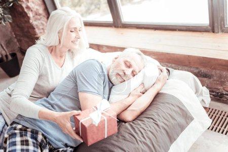 Photo pour Joli cadeau. Portrait d'une femme âgée agréable tenant un cadeau en main et attendant de faire un cadeau pendant que son mari dort paisiblement - image libre de droit