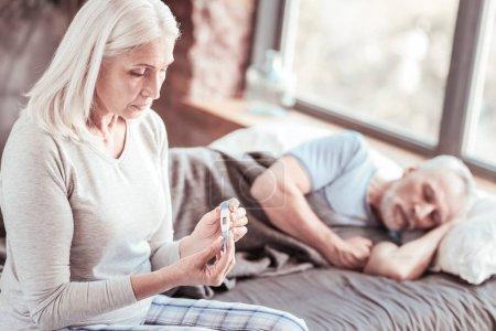 Photo pour Problèmes de santé. Portrait de femme âgée regardant thermomètre avec tristesse pendant que son mari dort au lit - image libre de droit