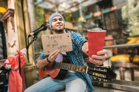 Photo for Great musician. Low angle of attractive male musician showing cardboard with inscription and stretching paper cup - Royalty Free Image
