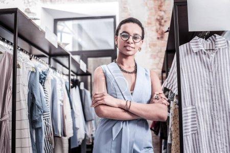 Photo pour Près des vêtements. Propriétaire attrayant élégant de la boutique portant de beaux accessoires et costume élégant debout près des vêtements - image libre de droit
