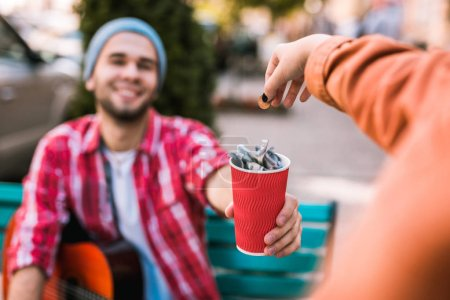 Photo for Here please. Selective focus of red paper cup hold by guy who smiling - Royalty Free Image