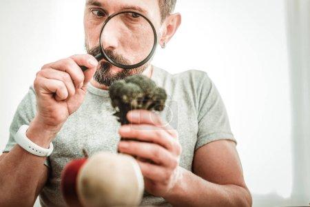 Photo pour Qualité de la nourriture. Homme intelligent sérieux regardant dans la loupe tout en vérifiant la qualité de la nourriture - image libre de droit