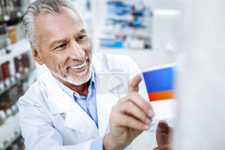 Photo pour Bon résultat. Pharmacien aux yeux foncés brûlé de soleil dans un manteau blanc souriant tout en préparant la vitrine de la pharmacie - image libre de droit