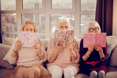 Three bookworms. Pleasant aged women looking at yo...