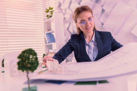 Photo pour Projet d'architecture. Architecte féminine satisfaite travaillant avec le plan et posant à la table - image libre de droit