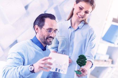 Photo pour Ingénieurs positives. Ingénieurs positifs souriant et se sentir intéressé tout en discutant des maisons et des arbres - image libre de droit