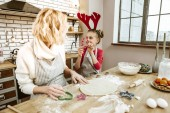 Girl fooling around. Interacted beaming child in red dress showing plastic form to her mother while they spending time in specious kitchen