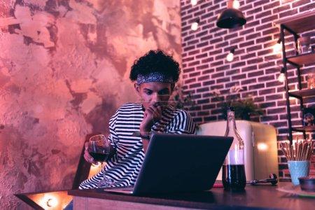 Photo pour Un film populaire. Jeune homme pensif avec un verre de vin cher dans la main droite assis près de la table et regardant un film d'intrigue sur l'ordinateur . - image libre de droit