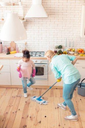 Photo pour Une fille qui aide. Petite fille mignonne portant un jean et une chemise rose aidant maman à nettoyer la cuisine - image libre de droit