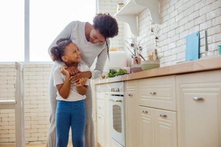 Photo pour Câlins chauds. Mignonne femme aux cheveux bouclés embrassant sa fille et debout ensemble dans la cuisine - image libre de droit