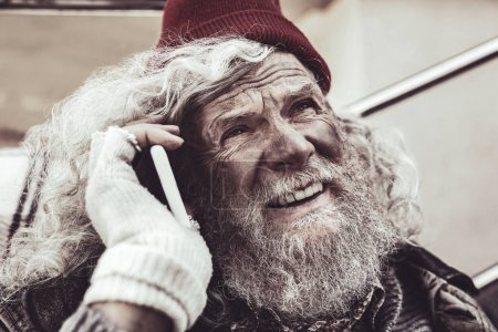 Photo for Private conversation. Portrait of homeless Caucasian man talking on smartphone and inspiredly looking at the sky. - Royalty Free Image