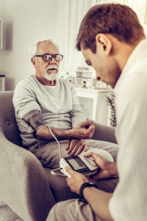 Photo for Measuring the blood pressure. Adult dark-haired son carefully taking the blood pressure with meter of his old silver-haired dad sitting in the chair - Royalty Free Image
