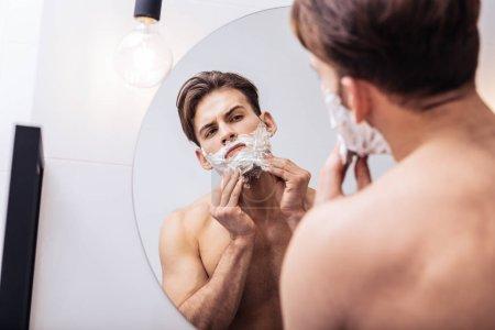 Photo for Wearing no shirt. Handsome dark-eyed man wearing no shirt using shaving foam before going to work - Royalty Free Image
