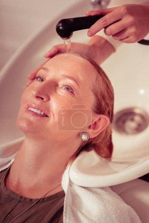 Photo pour Processus de beauté. Blonde joyeuse gardant sourire sur son visage tout en appréciant les soins capillaires - image libre de droit