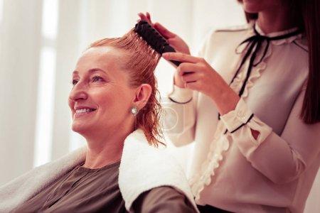 Photo pour Ne bougez pas. Maître professionnel debout derrière son client et peigner les cheveux avant la coupe de cheveux - image libre de droit