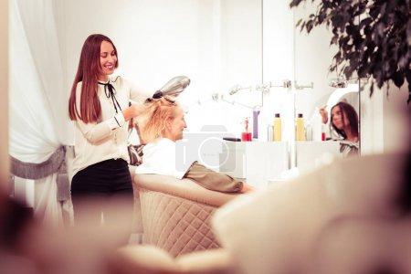 Photo pour Travaillez avec plaisir. Joyeux maître brunette garder sourire sur son visage tout en séchant les cheveux - image libre de droit