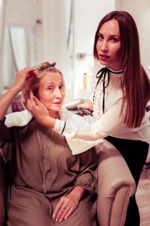 Photo pour Je comprends. Femme blonde ravie s'asseyant dans le fauteuil confortable et parlant à son coiffeur - image libre de droit