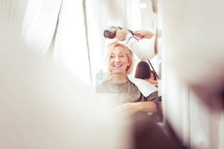 Photo pour Profitez du moment. Femme blonde étonnante gardant le sourire sur son visage tout en regardant son reflet - image libre de droit