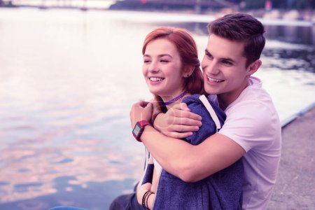Photo for Sharing warm hoodie. Strong smiling guy tightly hugging his pretty ginger girlfriend while spending date on the river - Royalty Free Image