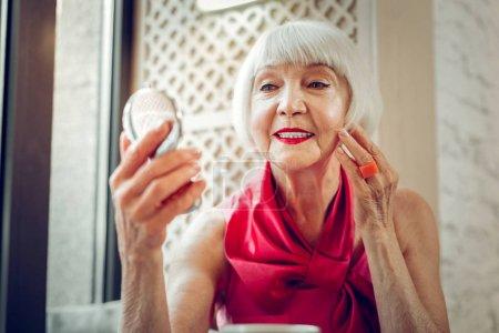 Miły w wieku kobieta patrząc na sama w The lustro