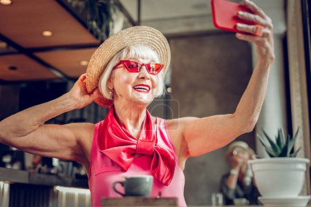 Photo pour Super photo. Femme âgée ravie touchant son chapeau tout en posant pour un selfie - image libre de droit