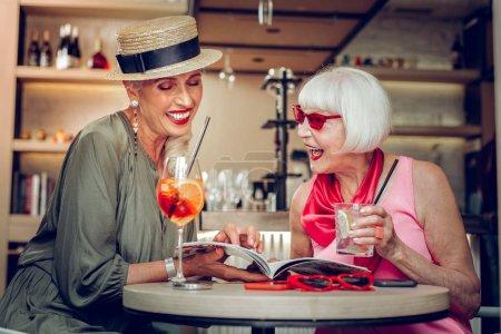 Photo pour Tendances de la mode. Joyeuses femmes âgées assises ensemble dans le café tout en lisant un magazine de mode - image libre de droit