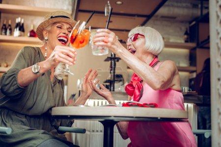 Photo pour À nous. Angle bas de femmes heureuses positives acclamant avec des boissons tout en étant assis ensemble à la cafétéria - image libre de droit