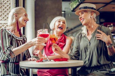 Photo pour Santé à nous. Joyeuses femmes âgées acclamant avec des lunettes tout en buvant des cocktails savoureux ensemble - image libre de droit