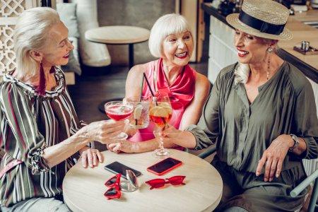 Photo pour Trois amis. Joyeuses femmes heureuses qui boivent des cocktails tout en se rencontrant au restaurant - image libre de droit