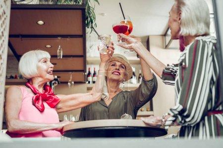 Photo pour Levant les verres. Angle bas des femmes âgées heureuses levant des verres avec leurs boissons - image libre de droit
