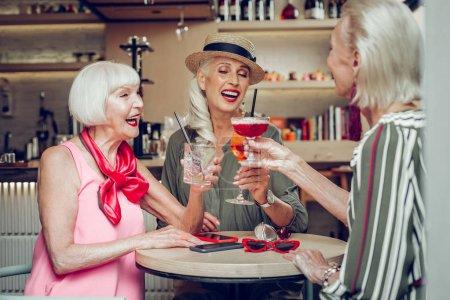Photo pour Notre fête. Femmes âgées positives parlant entre elles tout en ayant une belle célébration - image libre de droit