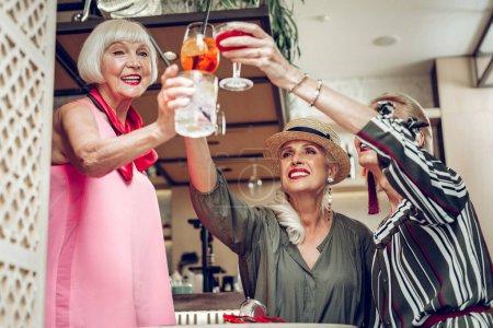 Photo pour Bonne humeur. Heureuses femmes âgées debout ensemble tout en claquant leurs lunettes - image libre de droit