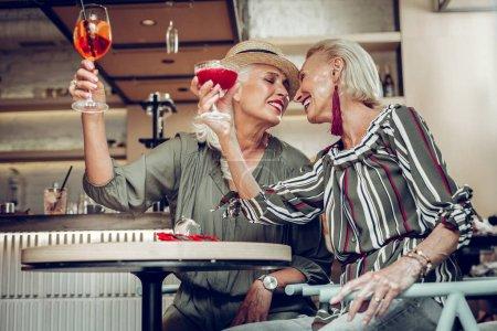Photo pour Meilleurs amis. Délicieuses femmes positives assises ensemble à la table tout en dégustant leurs boissons - image libre de droit