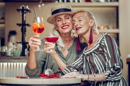 Photo pour Un regard rêveur. Belles femmes positives assises les yeux fermés tout en se souvenant de leur jeunesse - image libre de droit