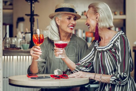 Photo for Pleasant communication. Happy nice women talking to each other while drinking cocktails - Royalty Free Image