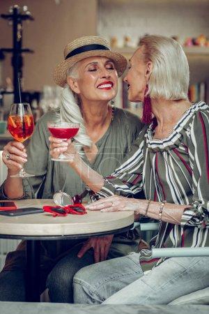 Photo pour Un moment agréable. Joyeuses femmes positives assises ensemble dans le restaurant tout en profitant de leur réunion - image libre de droit