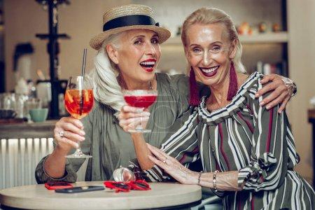 Photo pour Super rencontre. Délicieuses femmes élégantes buvant des cocktails ensemble lors d'une réunion dans le restaurant - image libre de droit