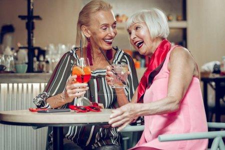 Photo pour Ravie de vous rencontrer. Bonnes femmes positives buvant des cocktails ensemble tout en s'amusant beaucoup - image libre de droit